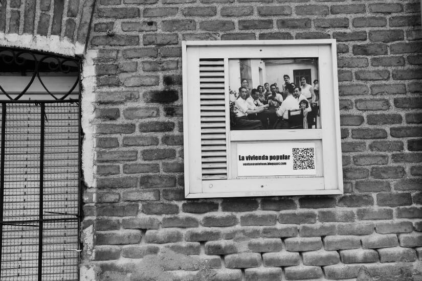 cartel en fachada sobre vivienda popular