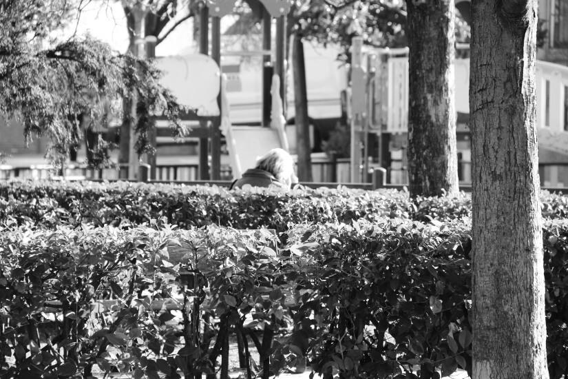mujer de espaldas sentada en u parque del barrio de tetuan en madrid